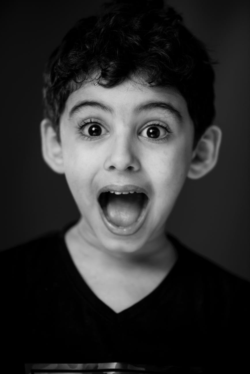boy in black v neck shirt with looking straight to the camera with a shocking face expression