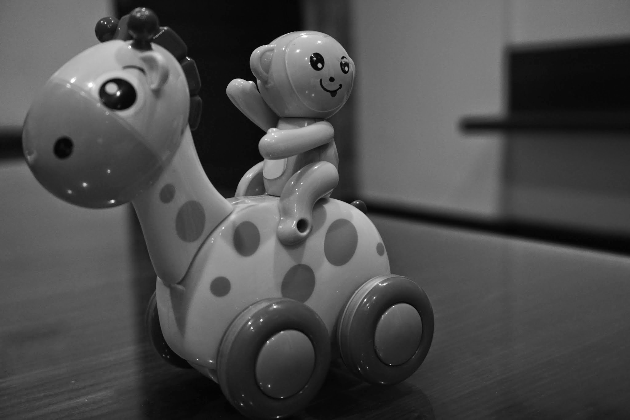 Canva - Grayscale Photo of Giraffe and Monkey Plastic Toy on Floor
